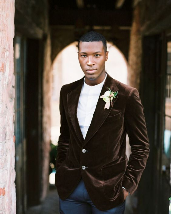a-casual-grooms-look-with-navy-pants-a-white-shirt-and-a-brown-velvet-blazer-for-a-modern-wedding